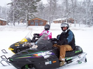 two people riding snowmobiles