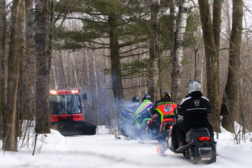 trail groomer and four snowmobilers on a trail