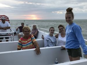 family in a boat at sunset