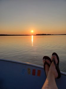 feet up on the side of a boat at sunset on a minnesota family resort vacation